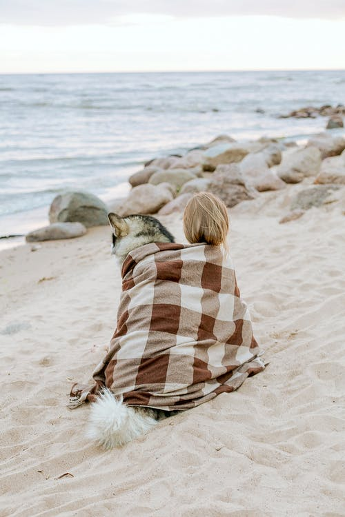 Woman in White and Brown Scarf Sitting on Beach with Dog