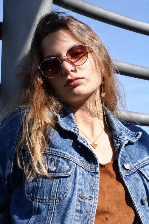 Woman in Blue Denim Jacket Wearing Sunglasses