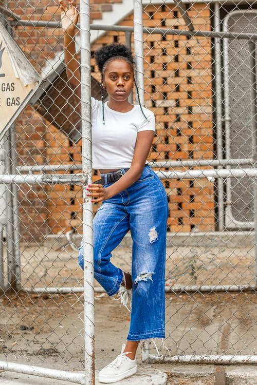 Woman in White Crew Neck T-shirt and Blue Denim Jeans Leaning on Metal Fence