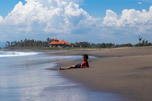 Child in Red Shirt Lying on Beach
