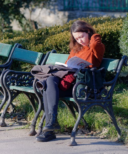 Woman in Red Long Sleeve Shirt and Gray Pants Sitting on Black Metal Bench Reading Book
