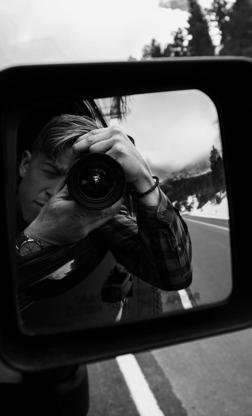Grayscale Reflection of Man Taking Photo Using Dslr Camera