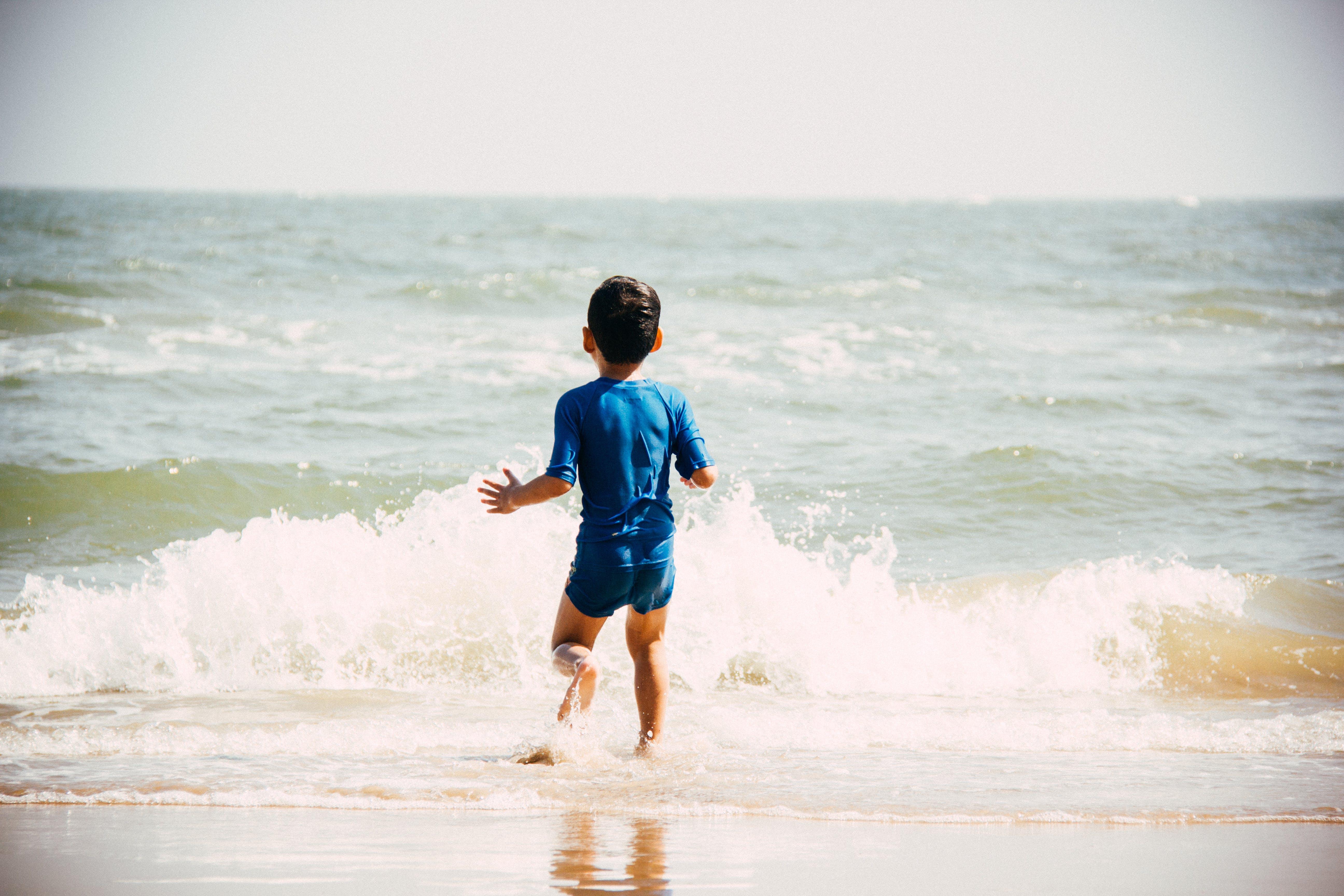 Boy Walking on Seashore