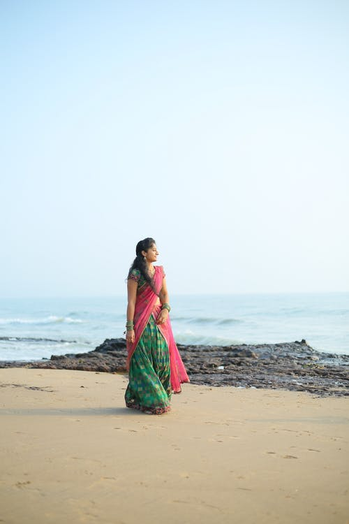 Woman in Green and Red Sari Standing on Beach