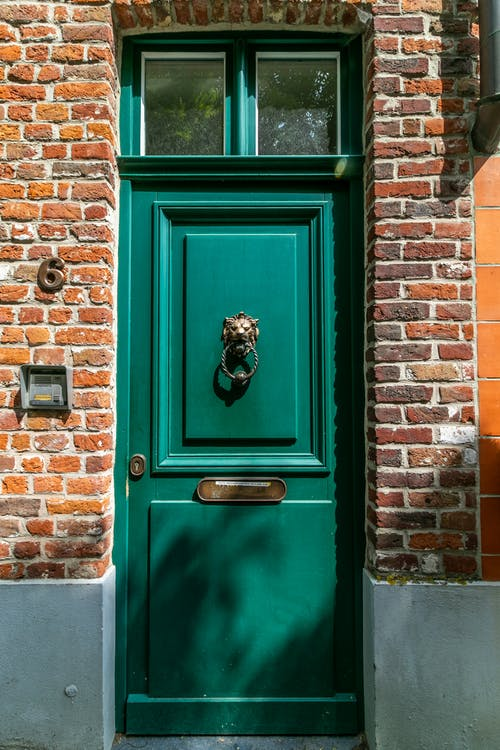 Green Wooden Door With Brown Brick Wall