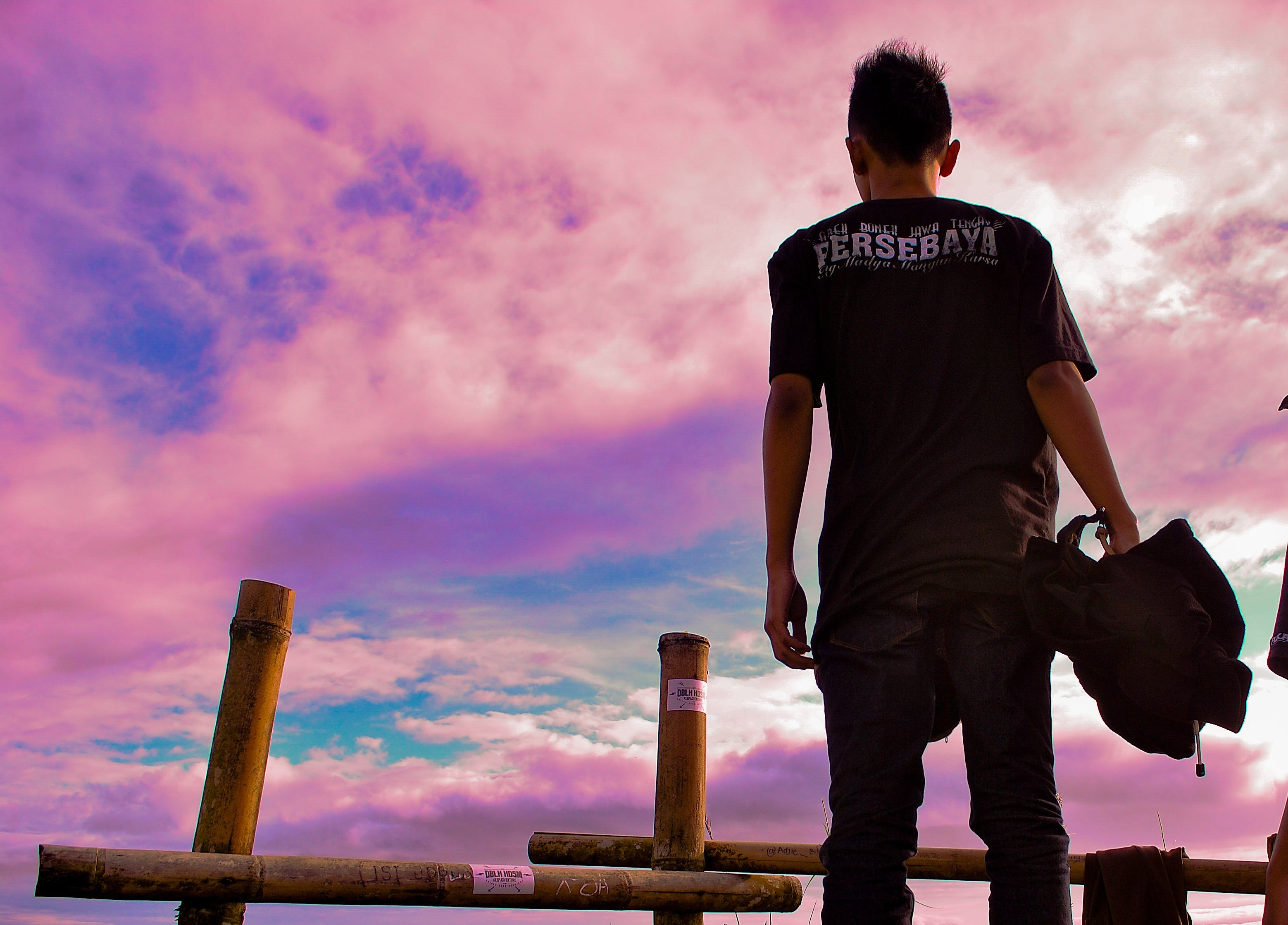 Man Wearing Black T-shirt Standing Near Bamboo Rack