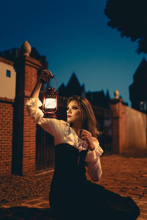 Woman in Black and White Long Sleeve Dress Holding Lamp