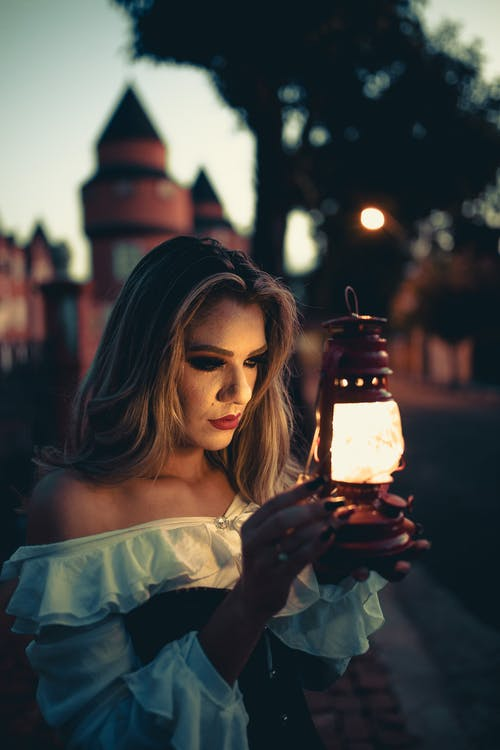 Woman in White Tank Top Holding Lit Lantern