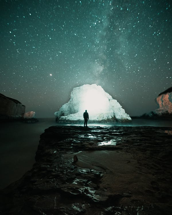Person Standing on Rock Formation Near Body of Water during Night Time