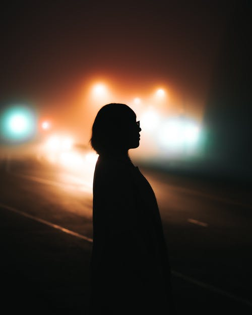 Silhouette of Person Standing on Road during Night Time