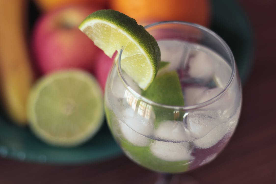 Close-up Photography of Green Sliced Lime on Clear Glass Cup