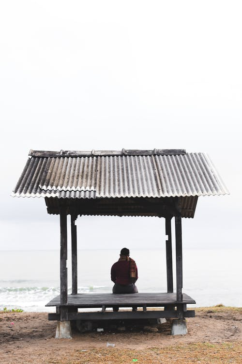 Man Sitting On A wooden Shed