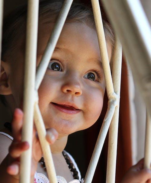 Smiling Baby Holding White Metal Frame
