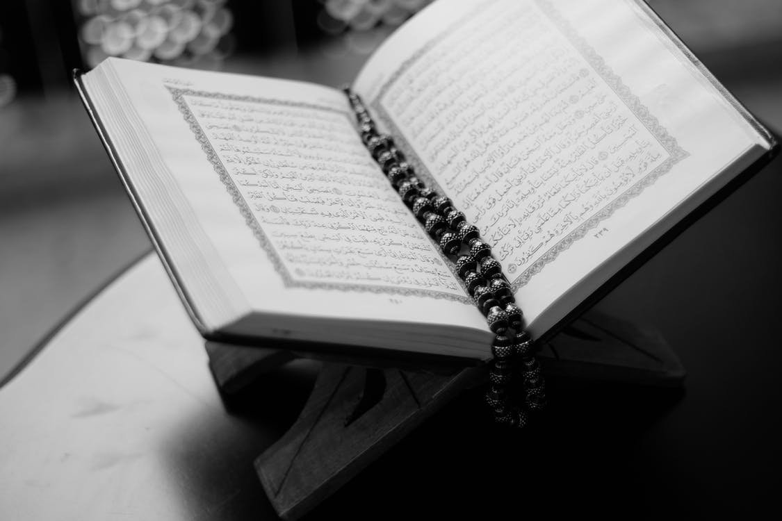 Grayscale Photo of Opened Qur'an