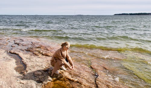 Woman in Brown Long Sleeve Shirt Sitting on Brown Rock Near Body of Water