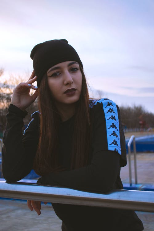 Woman in Black Top and Black Knit Cap While Leaning on Metal Railing