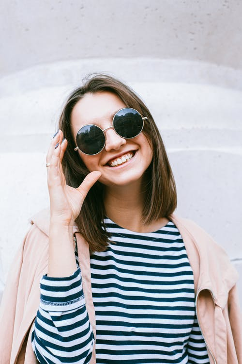 Woman in White and Black Striped Shirt Wearing Black Sunglasses