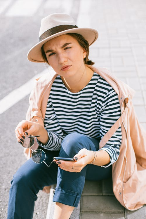 Woman in Black and White Striped Shirt and Brown Coat Holding Smartphone