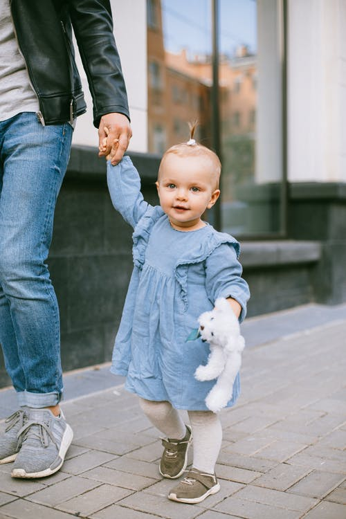 A Girl is Walking While Holding Her Fathers Hand