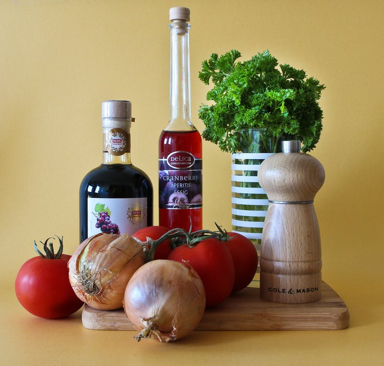 Brown Cole Mason Pepper Mill Near Red Tomatoes and Bottle