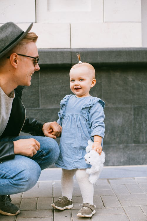 Man in Black Suit Jacket Holding Baby in Blue Denim Dress