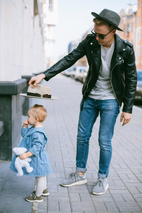 Man in Black Leather Jacket With Baby in Blue Dress Standing On Sidewalk
