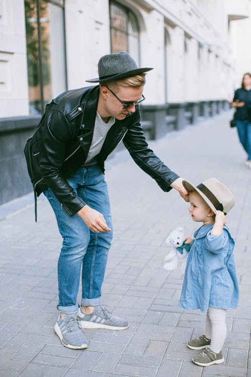 A Man In Black Jacket Staring at Her Daughter