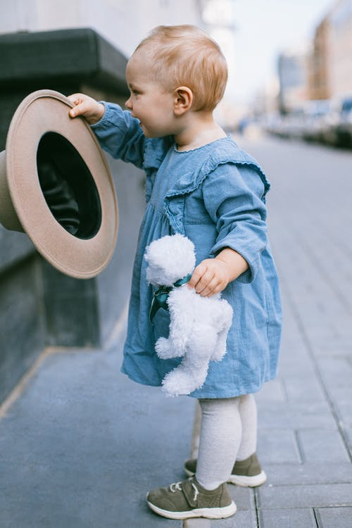 Photo of Baby Wearing Baby Clothes While Holding White Bear Plush Toy