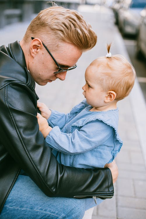 Man in Black Leather Jacket Carrying Baby in Blue Dress