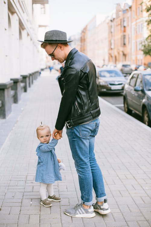 Father And Child Walking on Sidewalk