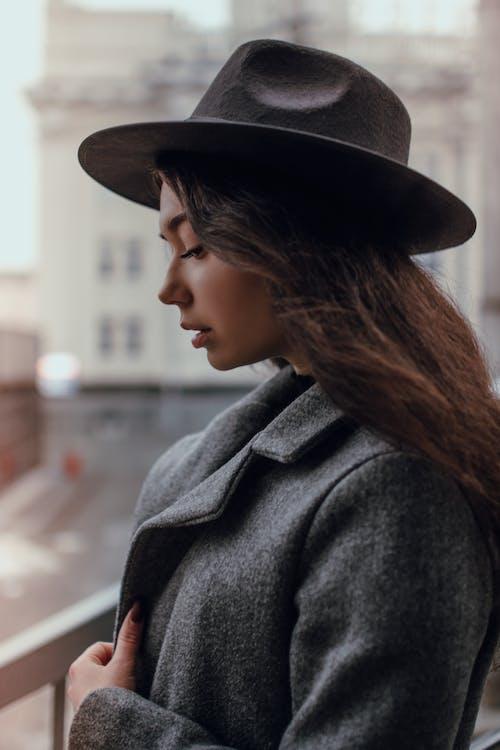 Woman in Gray Coat Wearing Brown Fedora Hat
