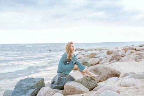 Woman in Blue Long Sleeve Dress Sitting on Gray Rock Near Sea