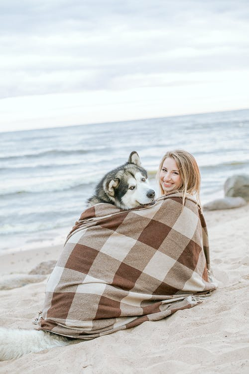 Woman in Brown and White Plaid Scarf Sitting on Beach