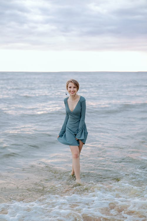 Woman in Teal Long Sleeve Dress Standing on Beach