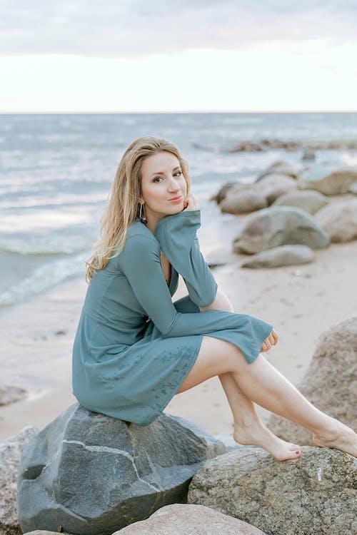 Woman in Gray Long Sleeve Dress Sitting on Gray Rock Near Sea