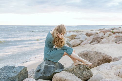 Woman in Teal Dress Sitting on Rock Near Sea