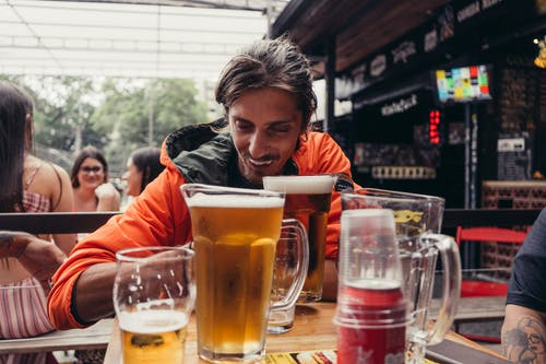Man in Orange Jacket Sitting Beside Table With Beer