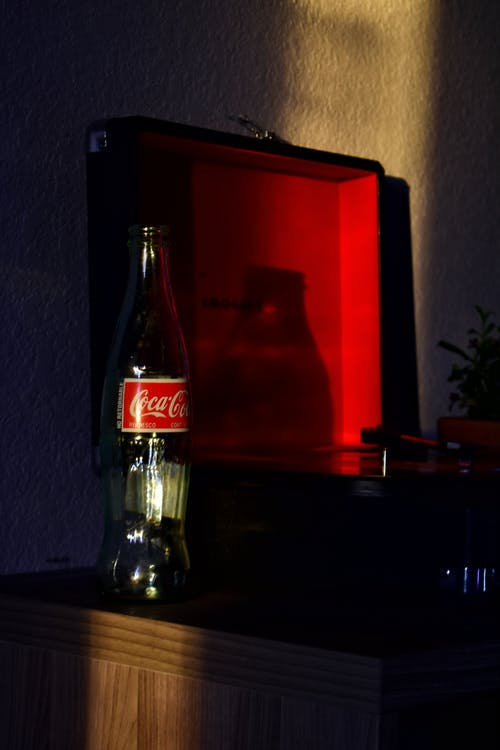 Coca Cola Glass Bottle on Brown Wooden Table