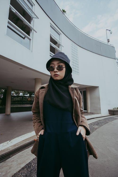 Woman in Black Hijab and Brown Coat Standing on Sidewalk