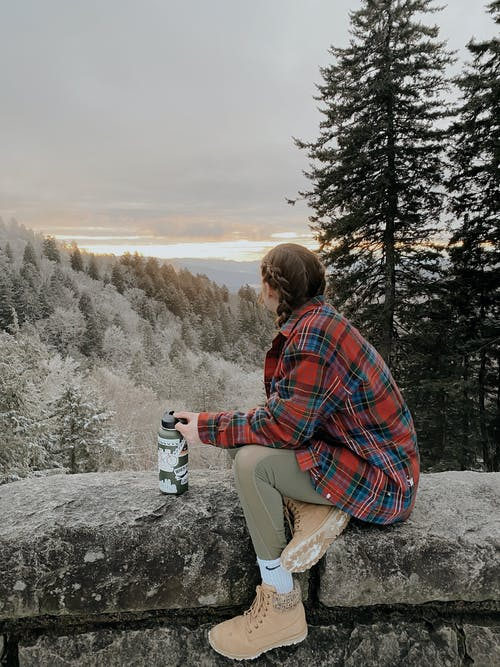 Woman in Red and Blue Plaid Shirt Sitting on Rock