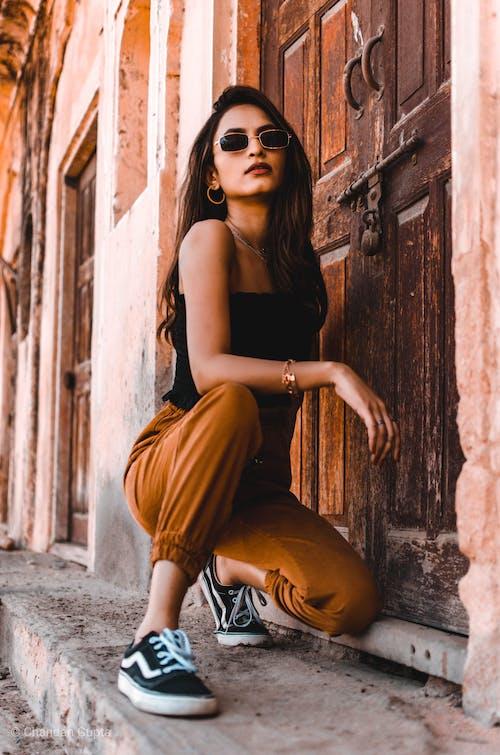 Женщина в солнцезащитных очках, стоя на коленях возле деревянной двери