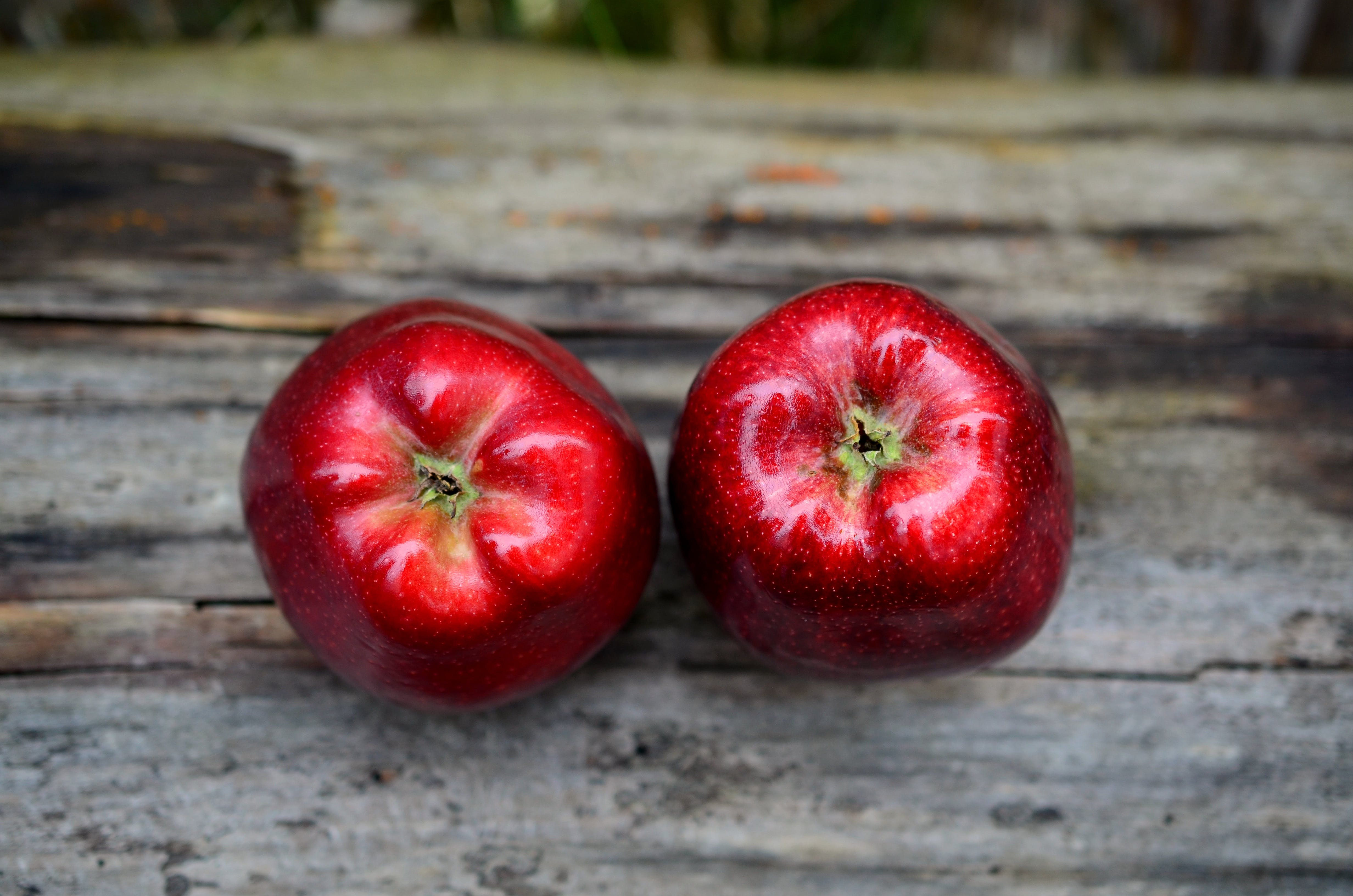 Two Red Fruits on Gray Wooden Surface