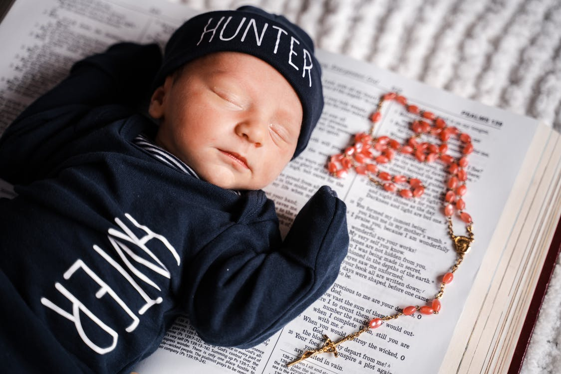 Baby Lying on Bible Near the Rosary