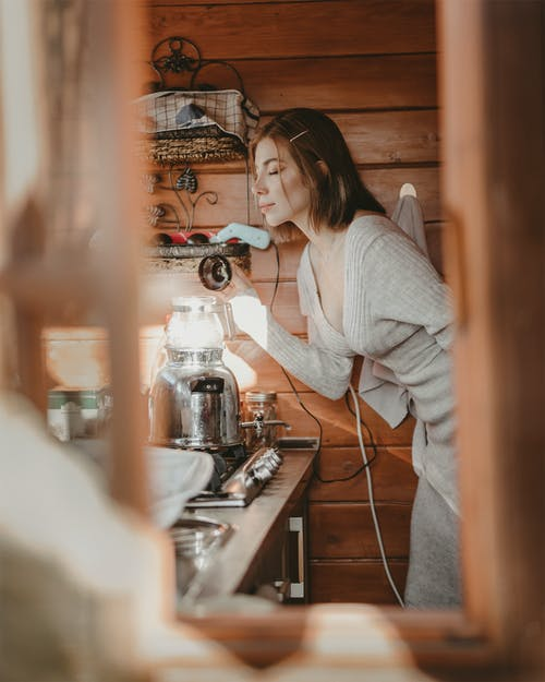 Woman in White Long Sleeve Shirt smelling Coffee in a coffee maker