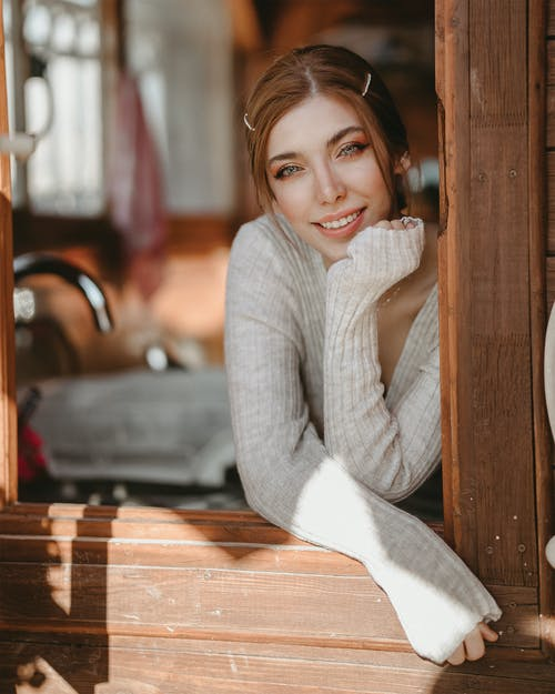 Woman Wearing Gray Sweater While Smiling