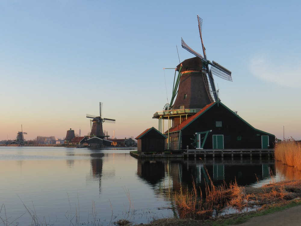 Brown and Black Windmill Beside Body of Water