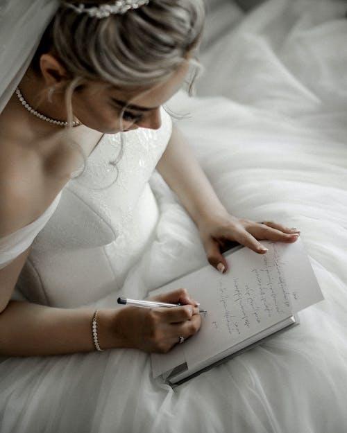 Woman in White Wedding Dress Writing on Book