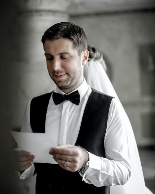 Man in White Formal Shirt and Black Waistcoat Holding White Paper