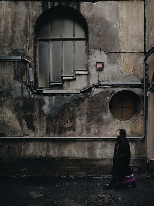 Woman in Black Coat Standing in Front of Window