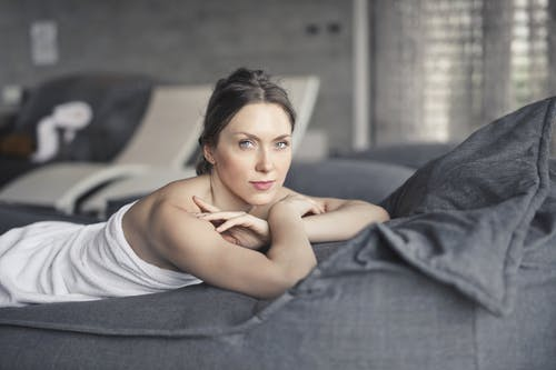 Woman Covered in Towel Lying on Bed